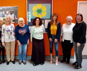 Group of female adults of varying ages stood smiling in front of orange wall