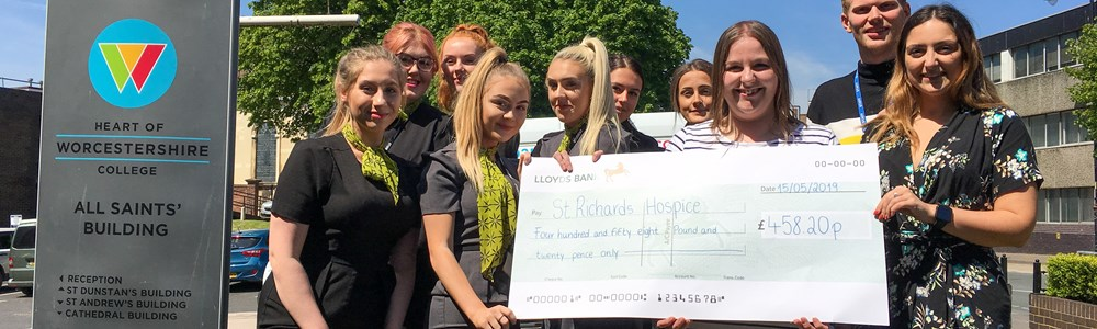 Group of students wearing travel and tourism uniforms stood outside and smiling next to HoW College sign whilst holding a giant cheque.