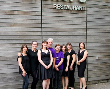Group of adults dressed smartly in black and purple. Stood smiling underneath Archer's Restaurant sign outside.