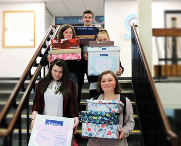 5 students stood on the stairs whilst holding colourfully wrapped boxes