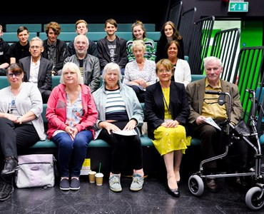 Group of senior adults and college students sat on green theatre benches in a black TV studio