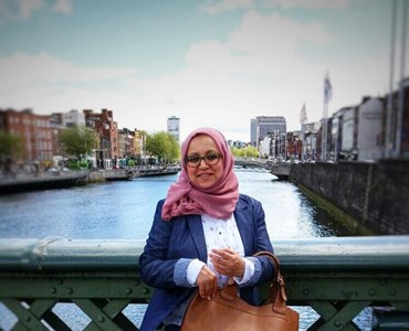 Female wearing a pink hijab and navy blazer stood holding a large brown leather handbag in front of a green bridge. Water and city can be seen in the background.