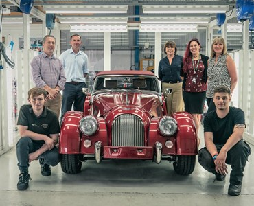 Males and females stood around a cherry red vintage car in a brightly lit white garage