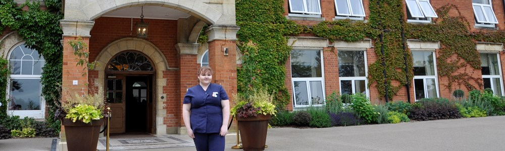 Female student in beauty therapy uniform stood outside large, country manor house