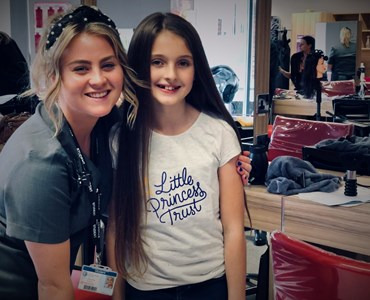 Beauty therapy student and little girl smiling in beauty salon. Little girl is wearing a tshirt saying Little Princess Trust.