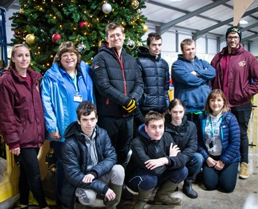 Group of students stood in front of a Christmas tree at a farm.