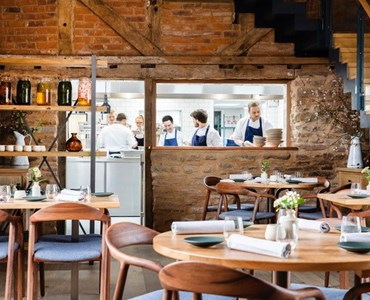 Photo taken inside a converted barn home to the Pensons restaurant. Tables and the kitchen are visible.