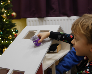 Male child in pajamas playing with a small purple toy and large wooden dolls house; Christmas tree is visible in the background.
