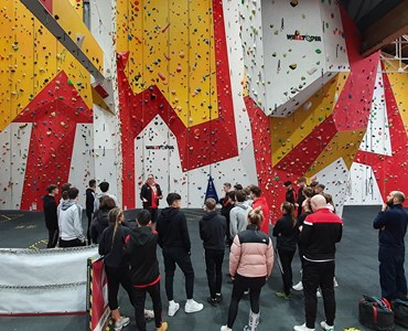 Large group of students with their back to the camera, in front of a large white, red and yellow climbing wall.