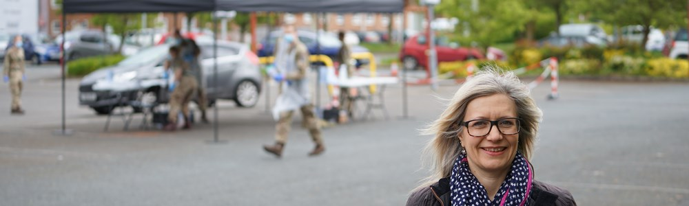 Female stood smiling in a car park with members of the army in the background directing people for Coronavirus testing