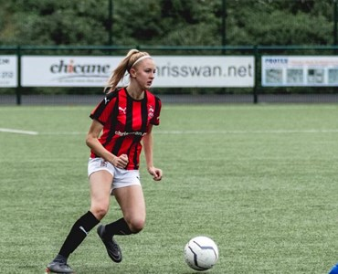Female playing football in red and black stripe jersey