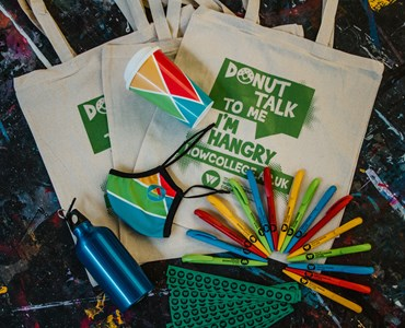 College of HoW College eco-friendly merch which includes Cotton canvas tote bag with the text Donut talk to me I'm Hangry, blue metal water bottle, green paper wristbands, HoW branded face covering, HoW branded reusable coffee cup and  red, green, blue and yellow pens