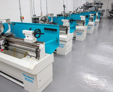 Row of grey and light blue machines in an engineering workshop.