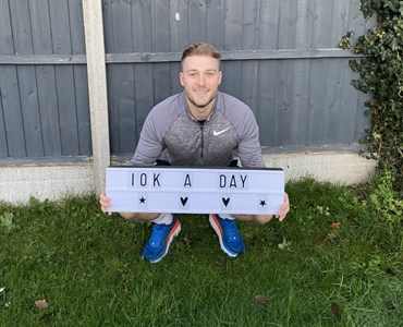 Image of male crouched in front of grey fence holding a white sign stating '10k a day'.
